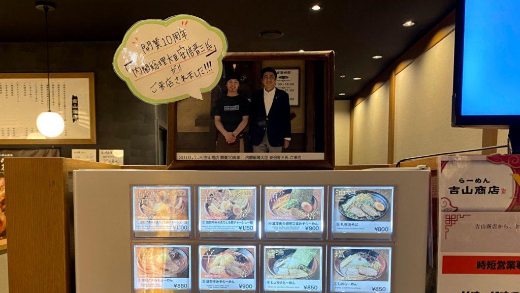 『吉山商店 なんばラーメン一座店』の券売機上に飾られた、安倍晋三前首相が来店した時の記念写真